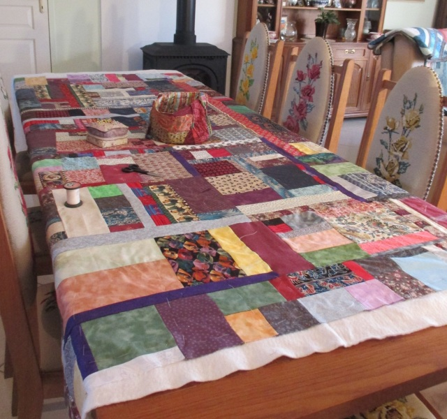 scrappy quilt being tacked